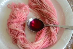 スプンで糸に染料をかけます
